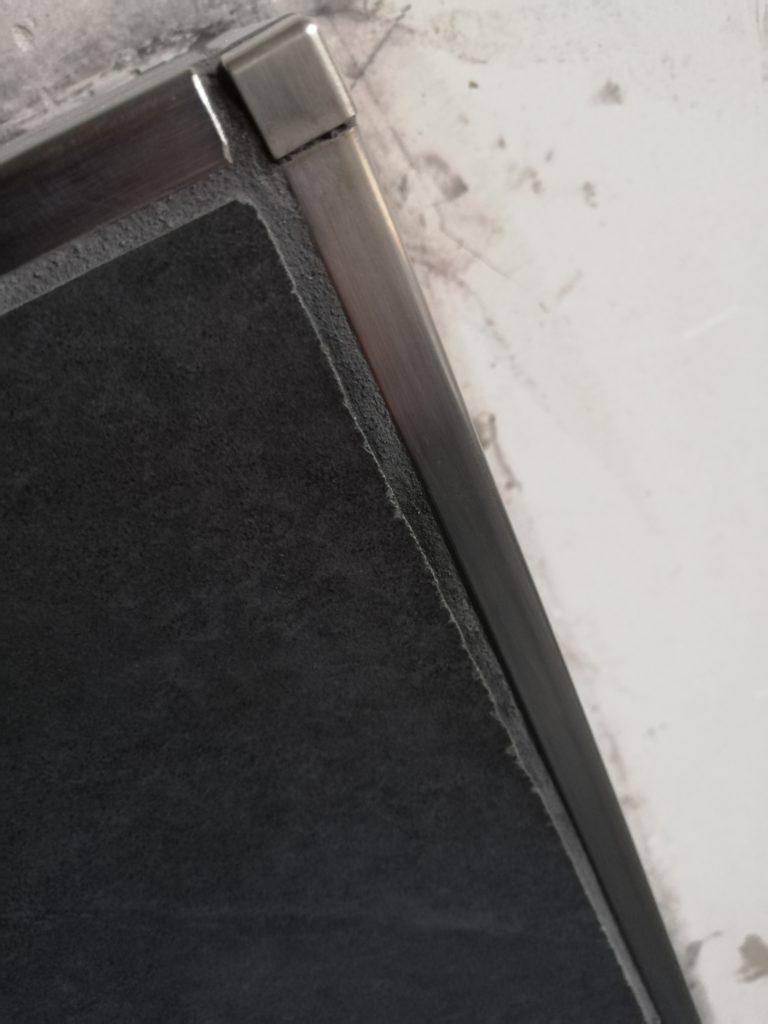Das Eckprofil ist schief und am Rand ist die Fliese abgeplatzt, weil das Werkzeug stumpf ist