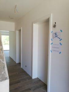 Flur mit Innentüren und Bauzeitenplan an der Wand